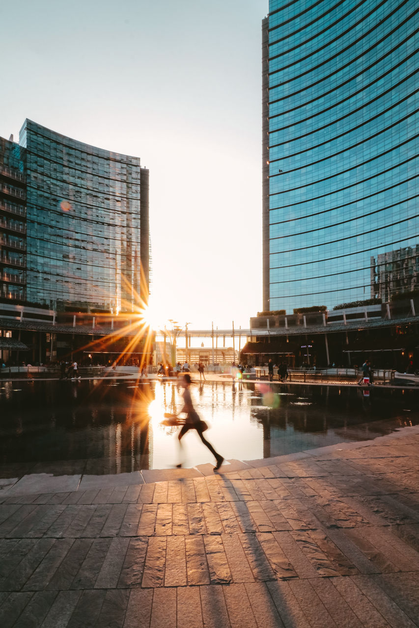 architecture, building exterior, built structure, real people, sunset, city, sunlight, sun, outdoors, one person, walking, women, clear sky, lifestyles, full length, sky, skyscraper, day, people
