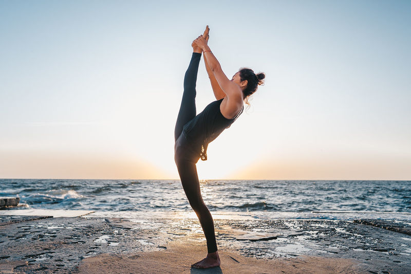 Full length of woman doing yoga at beach against sky during sunset