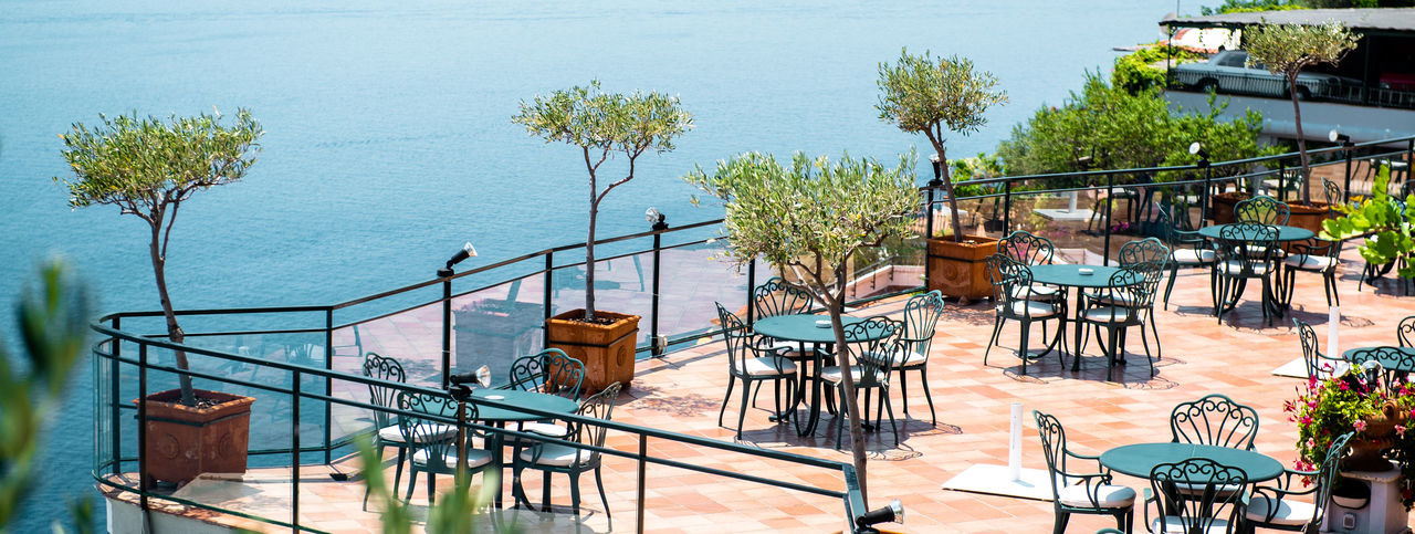 Mediterranean Sea Amalfi Coast Banner Beautiful Beauty In Nature Cafe Campania Catering Chair Coastal Day Empty Floor Furniture Holiday Horizontal Italy Landscape Marine Morning Nature Nobody Open Air Outdoors Panorama Panoramic Picturesque Positano Relaxation Resort Restaurant Scenic Seascape Seashore Seaside Season  Southern Summertime Table Terrace Tourism Touristic Travel Trees Tropical Tropics Turquoise Vacation View Water