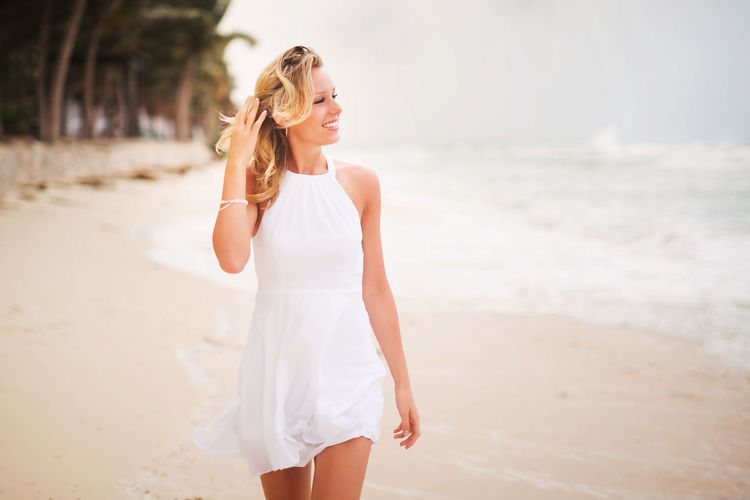 Beach Beautiful Woman Beauty Blond Hair Bride Focus On Foreground Front View Happiness Leisure Activity Lifestyles Long Hair Nature One Person Real People Sand Sea Smiling Standing Sunlight Three Quarter Length Vacations Wedding Dress White Color Young Adult Young Women