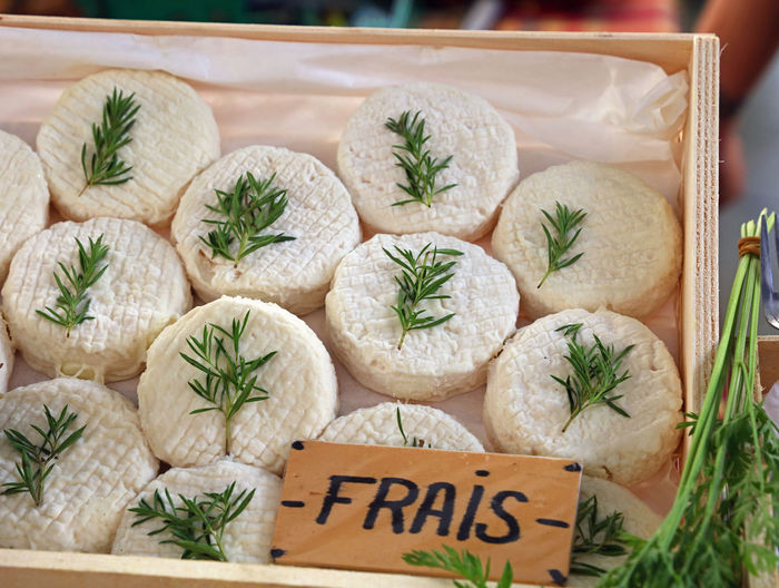 Close-up of cheese with herbs in box at market