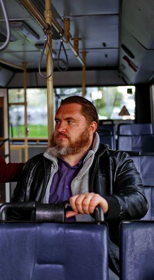 Transportation Sitting One Person Mode Of Transportation Vehicle Interior Portrait Seat Beard Travel Public Transportation Men Real People Adult Facial Hair Train Passenger Young Men Young Adult Warm Clothing