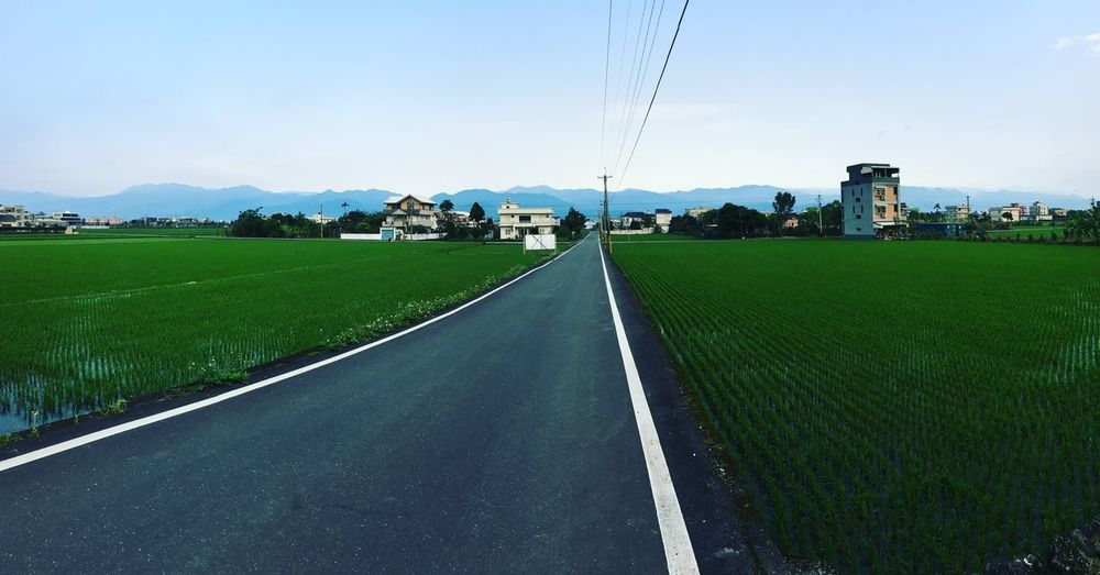 Road amidst field against sky in city