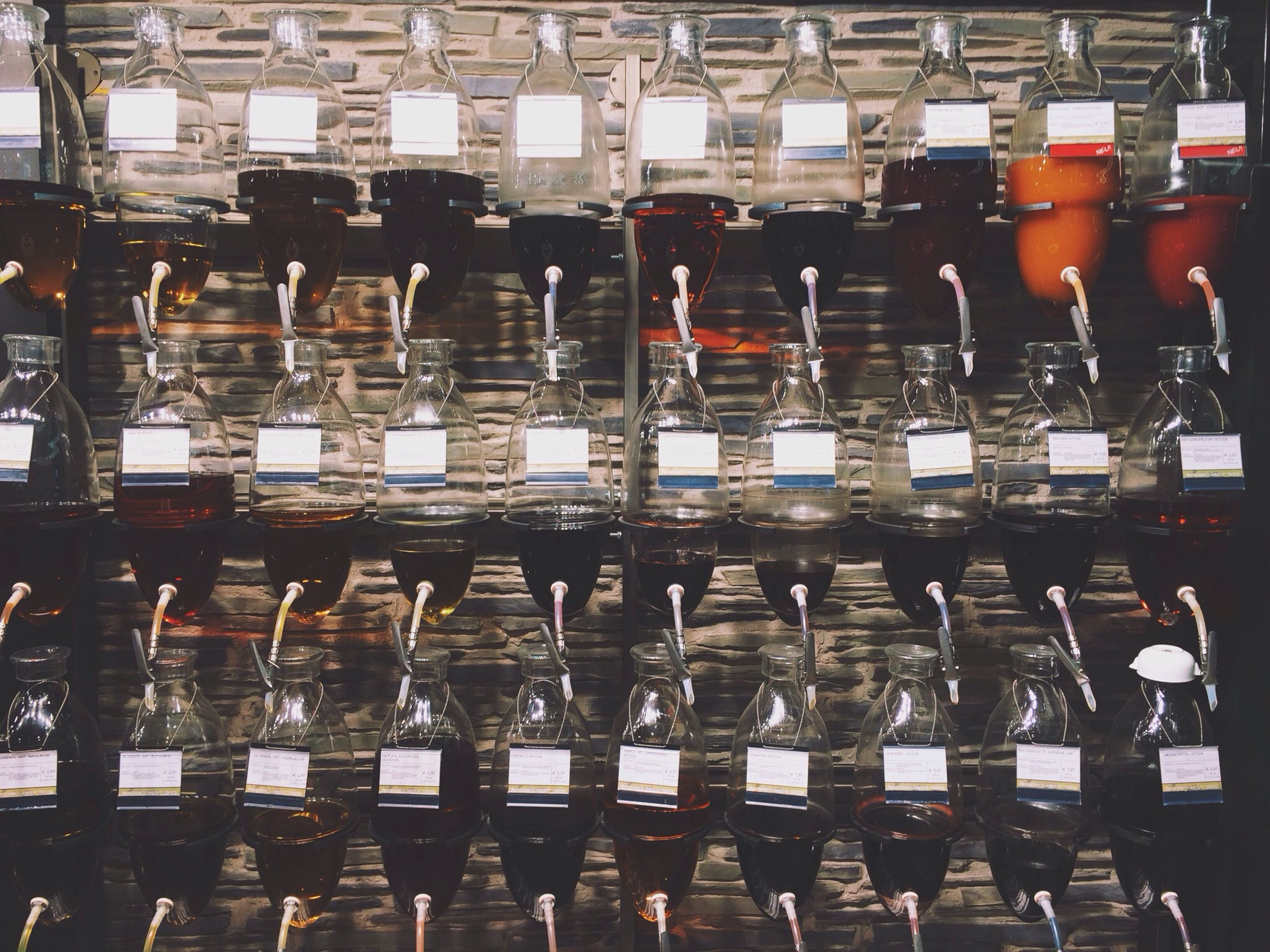 indoors, in a row, order, side by side, arrangement, large group of objects, abundance, repetition, chair, glass - material, restaurant, empty, retail, table, transparent, drink, illuminated, choice, men, food and drink