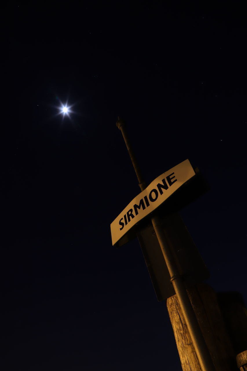 text, western script, communication, night, low angle view, no people, copy space, illuminated, sky, clear sky, sign, nature, lighting equipment, number, outdoors, direction, close-up, technology, information, street light