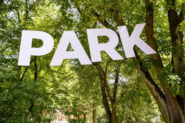 Welcome to the park Beauty In Nature Close-up Day Eye4photography  From My Point Of View Green Color Growth Information Information Sign Lush Foliage Nature No People Non-urban Scene Outdoors Text TheWeekOnEyeEM Tranquility Tree Tree Trunk Western Script