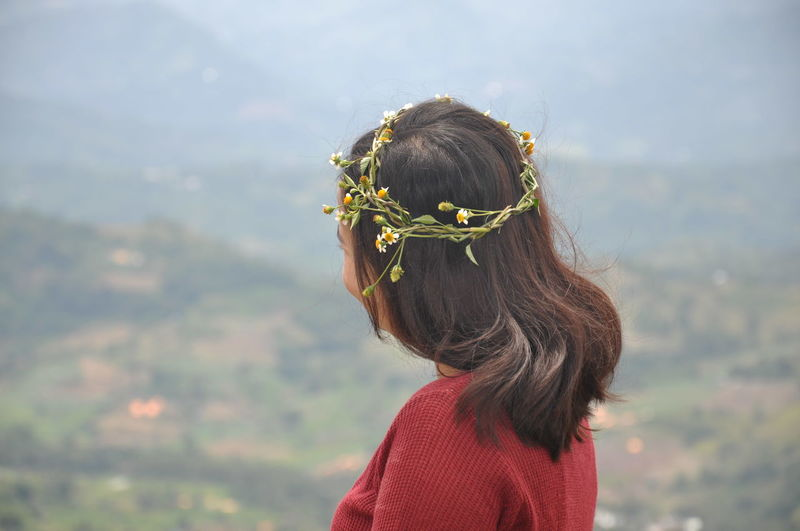 Young woman wearing floral wreath while looking at landscape