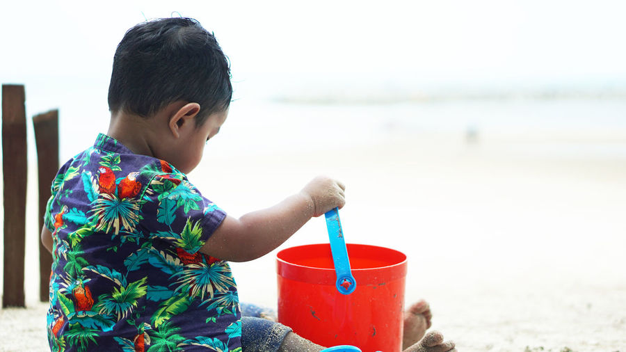 Side view of boy holding toy bucket while sitting at beach