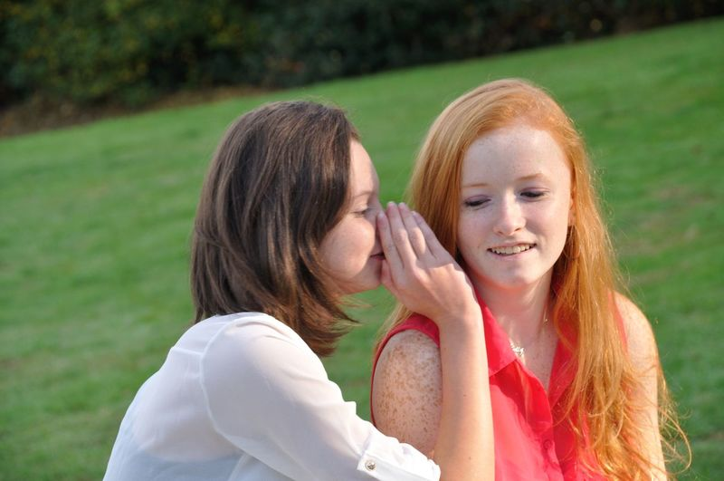 Woman whispering to female friend while sitting outdoors