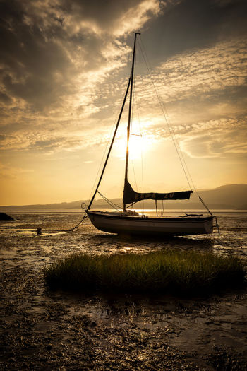 Sailboat Moored On Sea Against Sky During Sunset