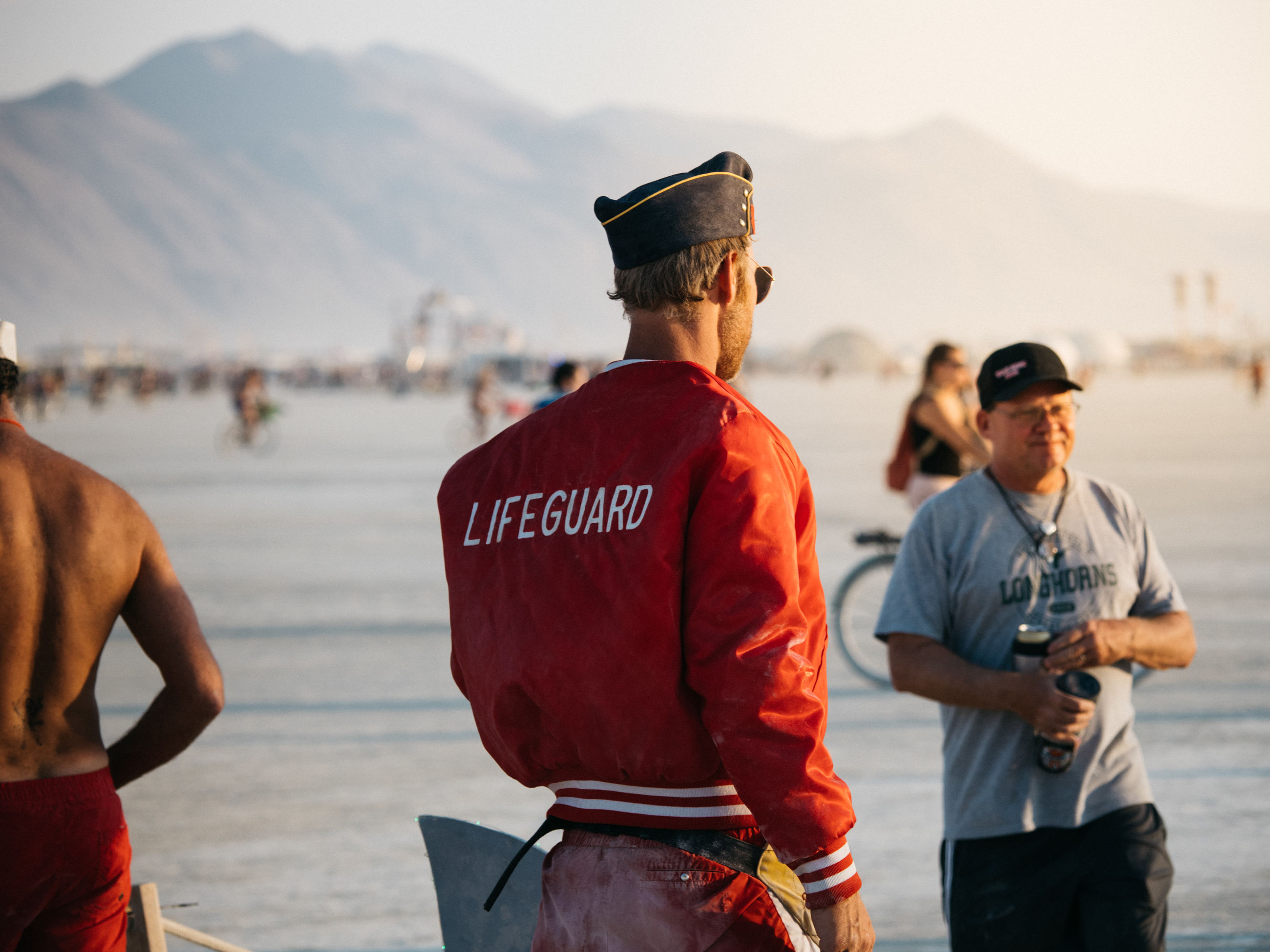 men, water, group of people, real people, focus on foreground, day, three quarter length, clothing, rear view, nature, standing, outdoors, hat, incidental people, people, adult, communication, males, cap, uniform
