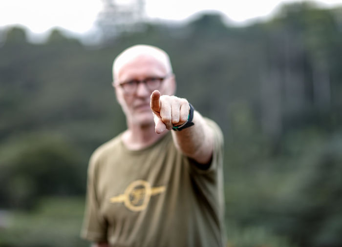 Portrait of man pointing at camera