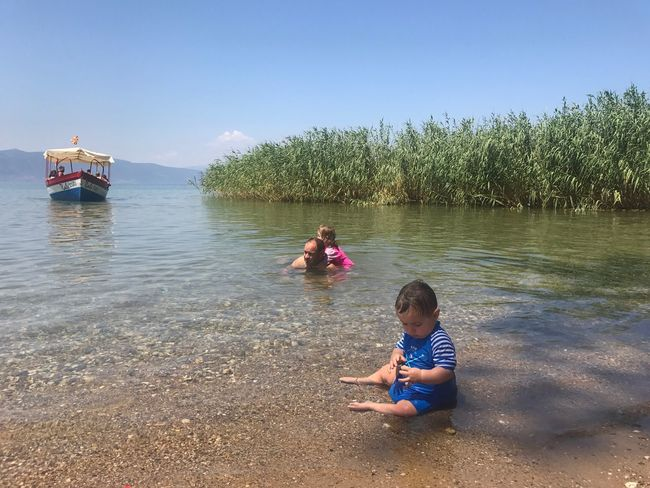 Ohrid Lake Lake Ohrid Family Childhood Boys Day Water Real People Leisure Activity Two People Sitting Nature Outdoors Elementary Age Lake Full Length Togetherness Sky Lifestyles Tree Child Beauty In Nature People