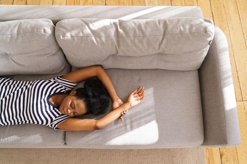 High angle view of baby lying on sofa