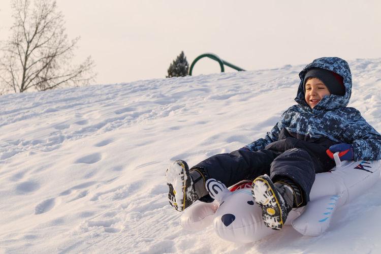 Full length of man sitting on snow