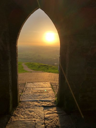 Sunlight History Arch Built Structure No People The Way Forward Old Ruin Architecture Sun Nature Sunset Sky Outdoors Beauty In Nature Day Grass Glastonbury Glastonbury Tor