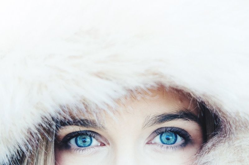 Cropped Image Of Woman With Blue Eyes Wearing Fur Hood