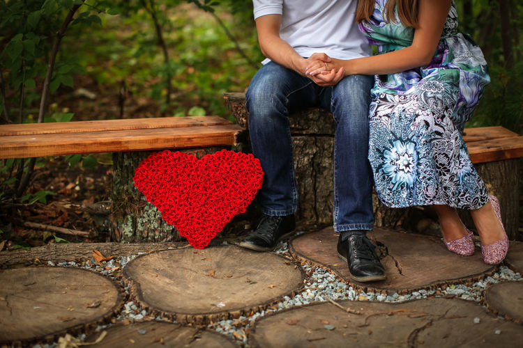 Low section of couple sitting on bench by red heart shape