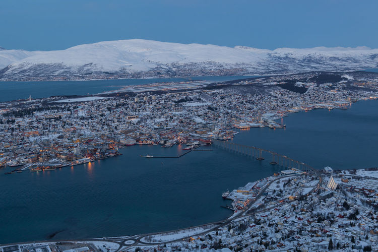 Aerial View Of Town By Fjord With Snowcapped Mountains Against Sky