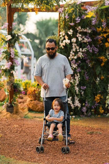 Man with daughter sitting in baby stroller at park