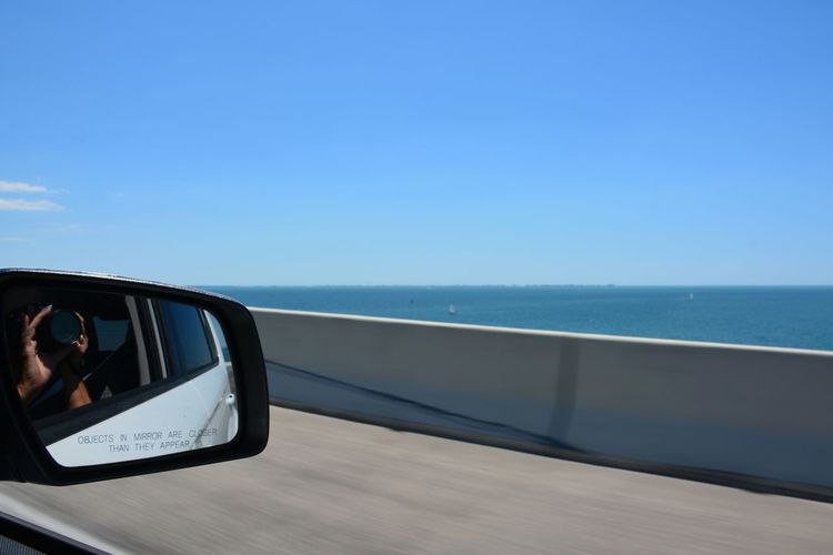 View from the passenger side riding over the Sunshine Skyway Bridge (I-275) Tampa Bay area Florida Horizon Over Water Side-view Mirror Clear Sky Vehicle Mirror Day Passenger Side View Side View Mirror Roadtrip Sunshine Skyway Bridge Passenger View Over The Bridge Scenics Blue Sky Driving Car Bridge - Man Made Structure Highway Tampa Bay