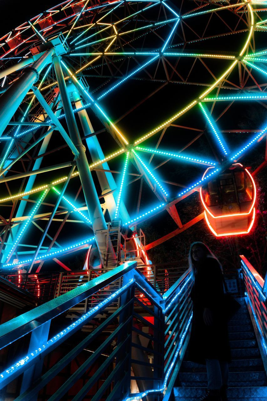 REAR VIEW OF PEOPLE STANDING AT ILLUMINATED AMUSEMENT PARK