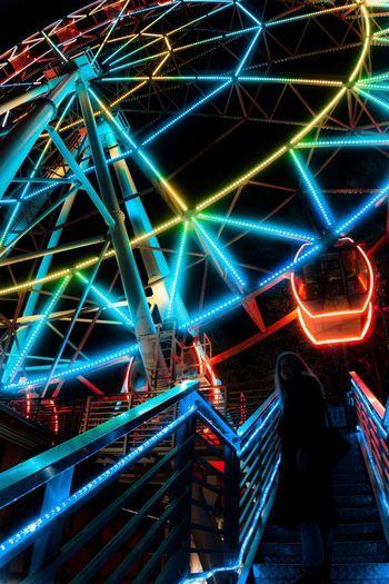 Rear view of people at illuminated amusement park at night
