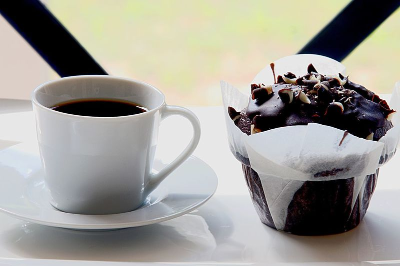 Close-up of coffee with chocolate chip cupcake on table