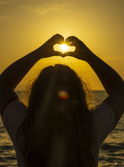 Portrait of woman with heart shape against sky during sunset