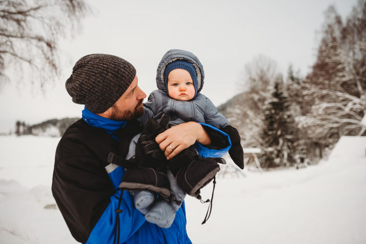 Father and son on snow during winter