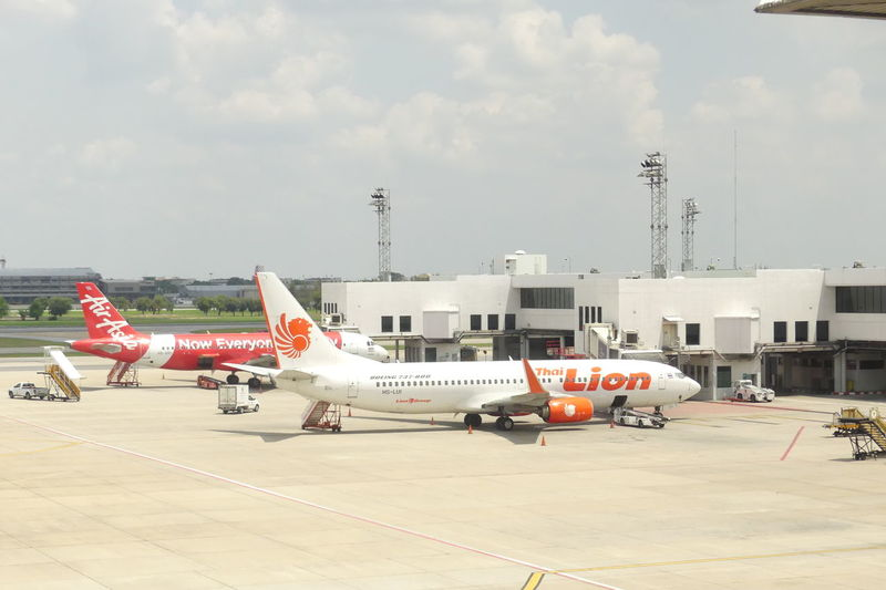 Bangkok, THAILAND - April 14, 2017 : Thai Lion Air & Air Asia in front off Terminal at Don Mueang International Airport on April 14, 2017. Thai Lion Air & Air Asia are Low-cost airline in Thailand. Air Asia X Air Vehicle Airplane Airport Airport Runway Airport Terminal Architecture Bangkok Thailand. Commercial Airplane Day Fight Low Cost Airlines No People Outdoors Runway Sky Thai Air Asia Thai Airpor Thai Lion Air Transportation Travel