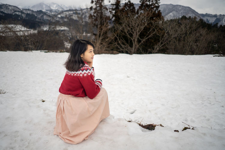 Girl crouching on snow covered land