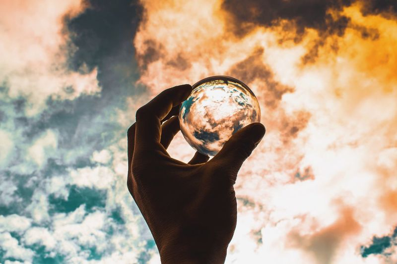 Cropped hand of man holding crystal ball against cloudy sky during sunset