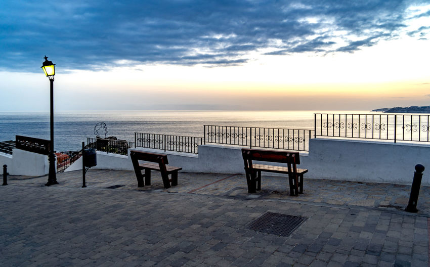 Sky Sea Water Seat Beauty In Nature Horizon Bench Cloud - Sky Horizon Over Water Sunset Street Nature Scenics - Nature Chair Street Light Architecture No People Empty Railing Promenade Outdoors Paving Stone