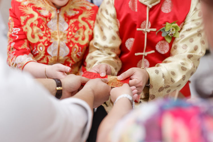 Chinese couple receivinv red packets as blessings Red Packet Blessing Human Hand Bridegroom Bride Women Togetherness Men Ceremony Wedding Dress Wedding Ceremony Wedding Groom Traditional Ceremony Newlywed