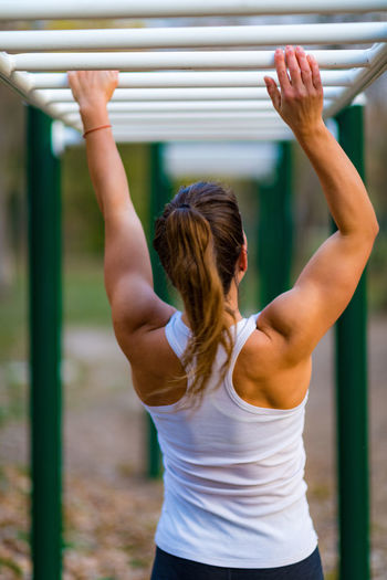 Rear view of woman exercising on monkey bars in park