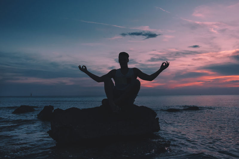 Full Length Of Man Meditating On Rock On Beach At Sunset
