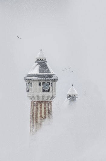 winter feeling Architecture Built Structure Building Exterior Cold Temperature Snow Winter Fog Tower Spirituality Building Tranquil Scene Minimalist Architecture Minimalism Bird Photography EyeEm Best Shots EyEmNewHere Factory Building Misty Foggy Morning Clock Tower Graphisoftpark Alone In The City  Old Buildings Freedom