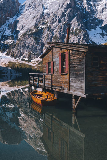 Boat moored by wooden cabin against snowcapped mountain