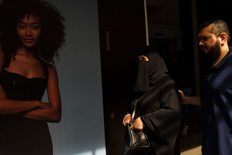 Couple walking by an onlooking poster Burka  Couple Culture Islam Juxtaposition Shadow Shadow And Light Streetphoto Streetphotography, Streetphotography_colors