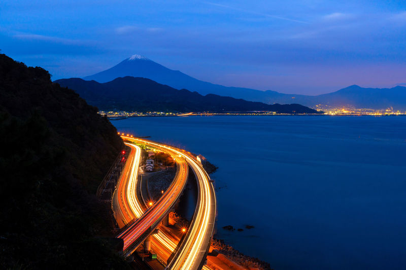 Light Trails On Road By Mountain Against Sky At Night