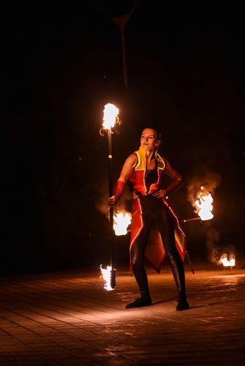 Woman holding illuminated fire burning at night