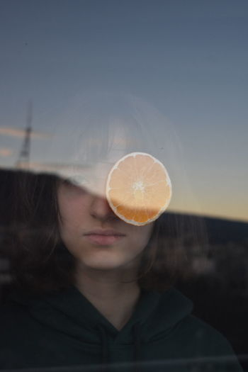 Woman and orange fruit seen through glass