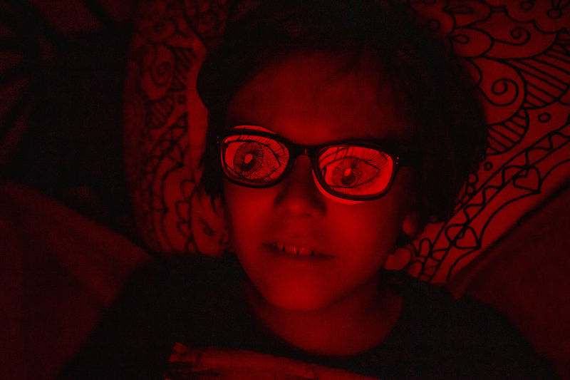 Close-up portrait of boy lying down on bed