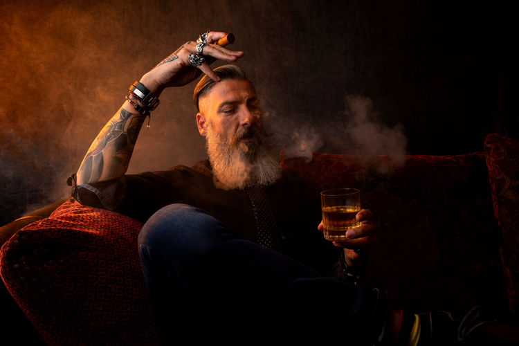 Mature Man Drinking Alcohol And Smoking Cigar While Sitting On Chair