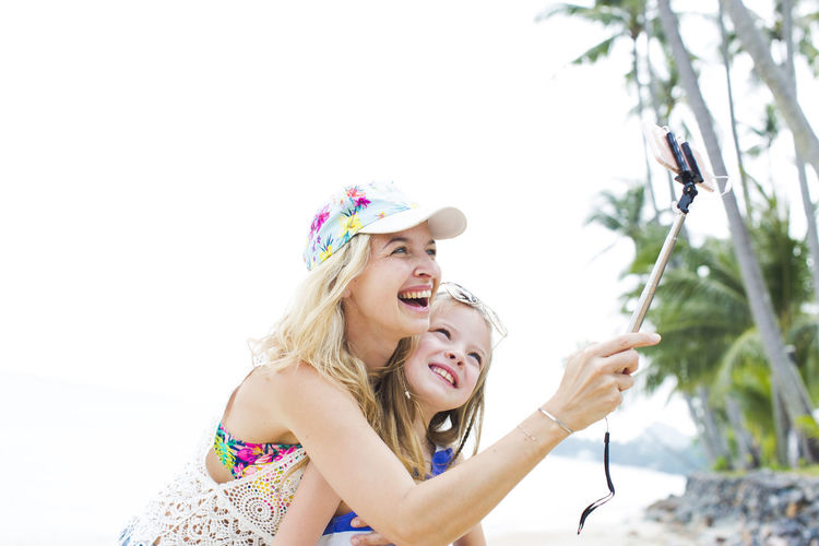 beautiful mother and her cute daughter doing a selfie photo with her phone on a beach in thailand Adult Blond Hair Bonding Childhood Day Friendship Fun Happiness Headshot Leisure Activity Lifestyles Nature Outdoors People Real People Smiling Togetherness Tree Two People Young Adult Young Women