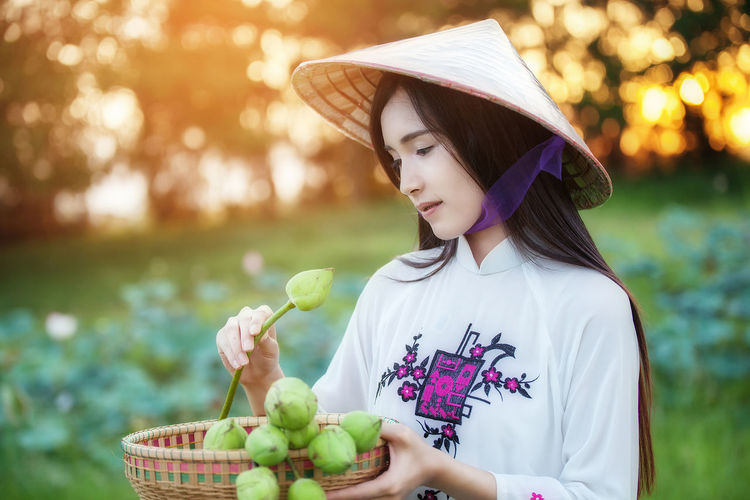 Woman dressed Vietnamese Vietnamese Basket Childhood Day Dressed Focus On Foreground Food Food And Drink Freshness Fruit Girls Grass Green Color Healthy Eating Healthy Lifestyle Holding Lifestyles Nature One Person Outdoors People Real People Young Adult