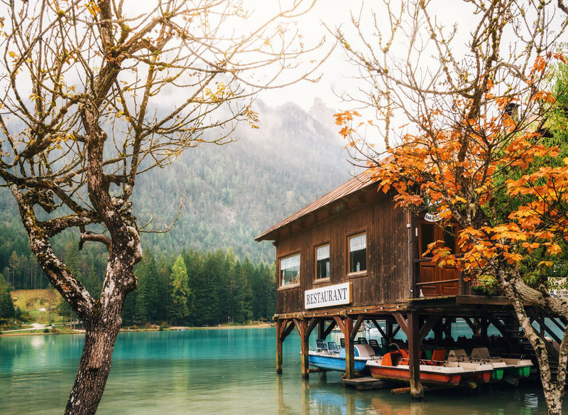 Italy. Dobbiaco Lake or Toblacher in Dolomites with wooden boathouse restaurant on stilts among trees in autumn Beauty In Nature Building Exterior Built Structure Houseboat Lake Mountain Nature Outdoors Scenics Tree Water Waterfront