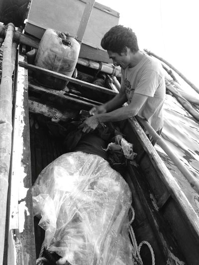 This fisherman's son was missing for two days after their fishing banca was hit by a Roll On Roll Off (RORO) vessel. Rescue operations were made but he was later found floating, lifeless, in Bacolod waters. The Photojournalist - 2016 EyeEm Awards Coverage EyeEm Eyeem Philippines EyeEm Gallery EyeEm Bnw Eyeem Photography Scene Emotions Fisherman Sea Father Tragedy Black And White Boat LifeLess Sea Tragedy Sea Mishap Fishing Banca Philippines Monochrome Photography