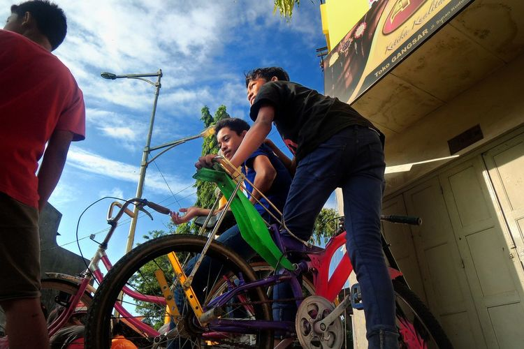 Low angle view of friends with bicycles against sky
